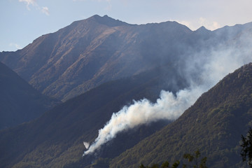 Fire fighting efforts are under way with helicopters to put out forest fires above Gordola, Ticino, Switzerland, on April 19th, 2017