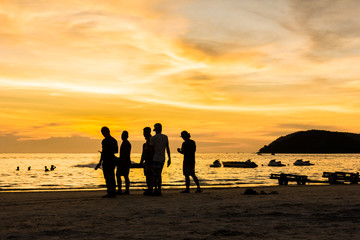 group of people watching the sunset on the beach