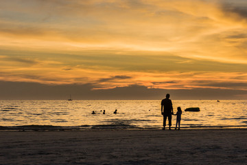 father and daughter watching the sunset on the beach