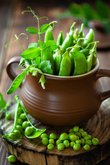 Fresh green peas on dark wooden rustic background