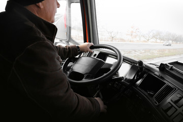 Elderly man driving big modern truck