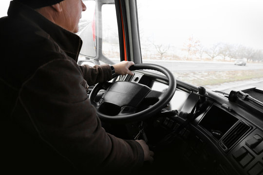 Elderly man driving big modern truck