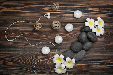 Beautiful spa composition with earphones on wooden background