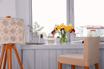 Windowsill with beautiful flowers and home plants