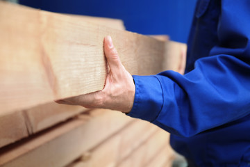 Carpenter with wooden planks in workshop, closeup