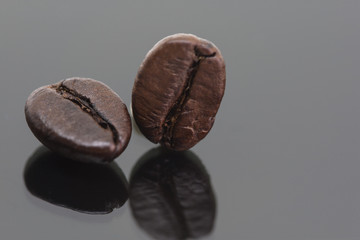 Coffee bean with reflex isolated on black background.
