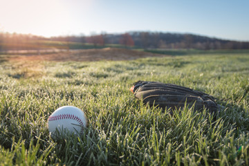 Baseball glove and ball on field in early morning grass and dew as sun rises in background