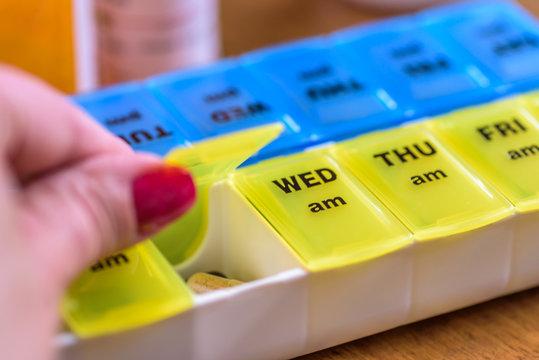 closeup of a woman's hand opening a pill box