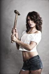 Sexy girl repairman holding hammer tool