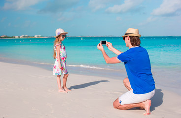 Young father taking photo on cellphone of his kid on the beach