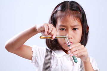 Little girl holding a test tube with liquid Scientist chemistry and science education concept