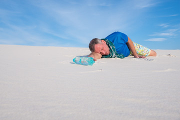 Exhausted traveler lies in the middle of the desert next to a bottle of water