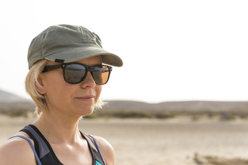 Lady Wearing Sunglasses Looking Away with Desert and Hills Background