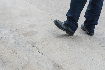 Leg of man with long black trousers standing on the street., security guard men shoes stand on walking street