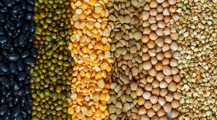 Cereals background: chickpeas, peas, lentils, green buckwheat, black beans, sesame seeds.