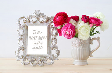 bouquet of spring flowers next to blank vintage photo frame