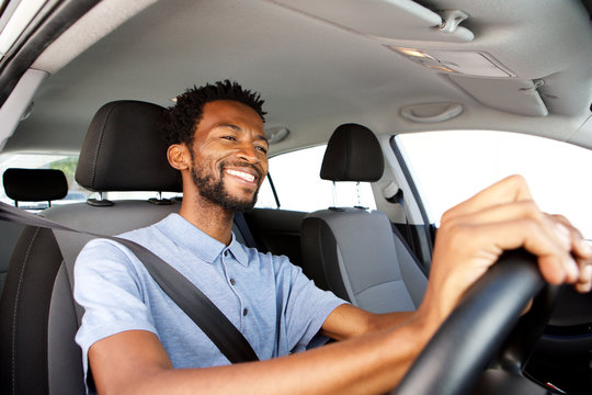 Close up happy african american man driving car
