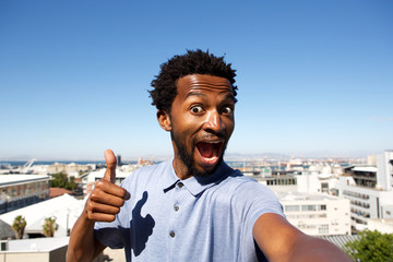 african american man standing by urban background with thumb up