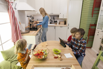 Children sitting at the table and waiting for their mother to cook dinner. Two boys using Wireless Tablet.