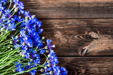 Floral frame with blue flowers on wood, copy space