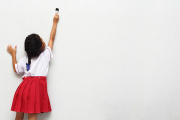 little girl with paintbrush on wall, back view