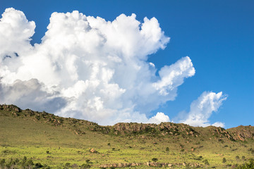 Lurking clouds on a blue summer sun sky creeping over rocky green hills