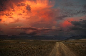 Road path on a desert wild mountain plateau at the background of the hills under a dramatic sunset colorful sky with illuminated red pink purple clouds Kurai Altai Mountains Siberia Russia