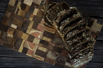 Black bread with seeds and sesame seeds on a board of wooden logs