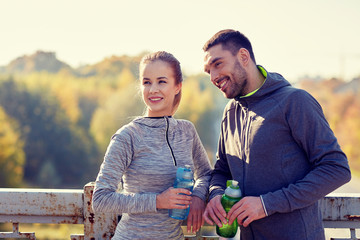 smiling couple with bottles of water outdoors
