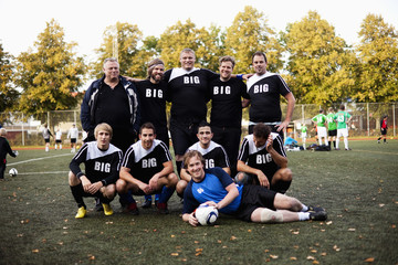 Portrait of happy soccer team at field