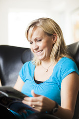 Smiling woman reading magazine while sitting on chair at home