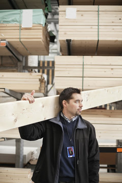 Man carrying wood while looking away at lumber industry