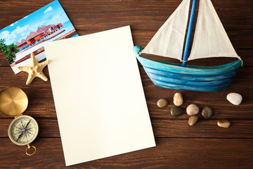 Travel concept. Blank notepad page, compass and cute sea decorations on wooden background