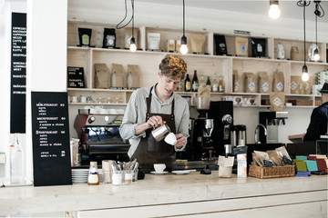 Young barista preparing cappuccino at counter in coffee shop