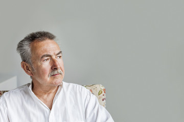 Senior man sitting against gray wall at home