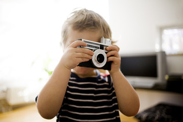 Boy using vintage camera at home