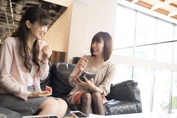 Two women are talking happily watching smartphone