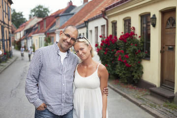 Portrait of happy mid adult couple standing on street in town