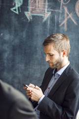 Businessman using smart phone in creative office