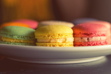 Colorful multicolor sweet delicious macaroons on dark background. Shallow depth of field. Coloring toned photo.