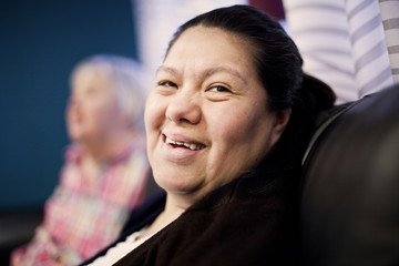 Close-up portrait of smiling woman with down syndrome resting at nursing home
