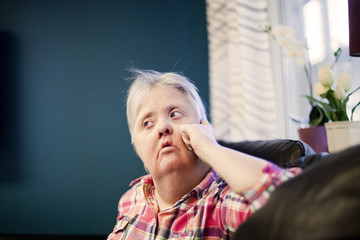 Thoughtful mature woman with down syndrome looking away while resting on sofa