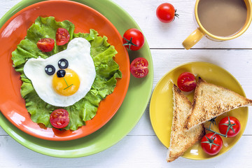Funny Breakfast with bear-shaped fried egg, toast, cherry tomato, lettuce on colored plates and coffee.