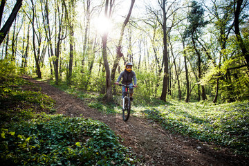 man ride mountain bike through forest
