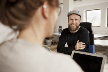 Portrait of smiling businessman sitting with woman at desk in office