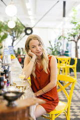 Portrait of young woman with hand on chin while sitting at counter in cafe
