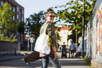 Portrait of happy woman carrying skateboard on sidewalk