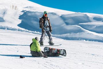 snowboarder trainer teach man sitting with snowboard
