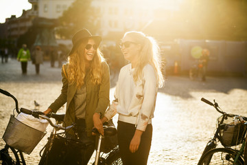 Cheerful female friends with bicycles talking on city street during summer