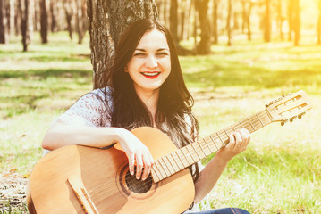 woman playing an acoustic guitar outdoor